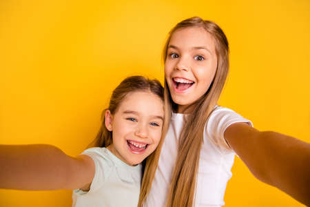 Self-portrait of nice-looking cool cute crazy attractive lovely winsome cheerful cheery positive emotional pre-teen girls having fun isolated over bright vivid shine yellow background