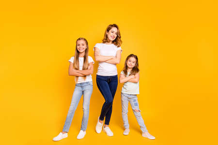 Full length body size view portrait of three nice attractive slim cheerful cheery people folded arms mum mommy isolated over bright vivid shine yellow background Фото со стока