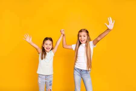 Portrait of two nice cool crazy attractive lovely cheerful cheery positive girlish girls holding hands having fun isolated over bright vivid shine yellow background