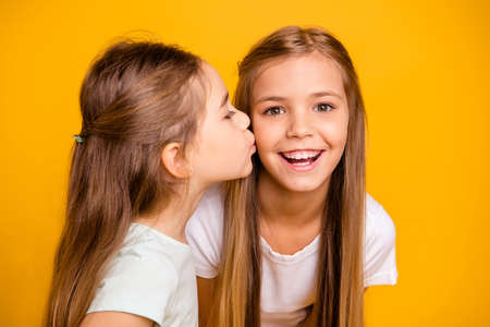 Close-up portrait of two nice cool attractive lovely sweet cheerful cheery positive girlish girls having fun kissing care isolated over bright vivid shine yellow background