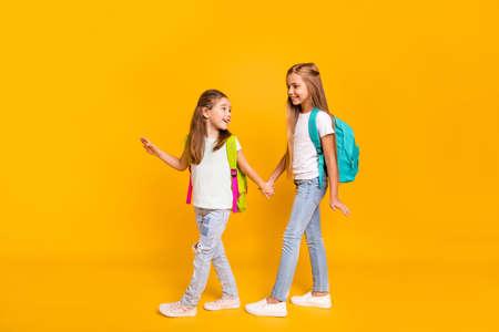 Vue sur toute la longueur du corps de deux jolies filles pré-adolescentes intelligentes et gaies, attrayantes et intelligentes, avec des sacs à dos colorés, se tenant la main à l'école isolée sur fond jaune brillant et brillant