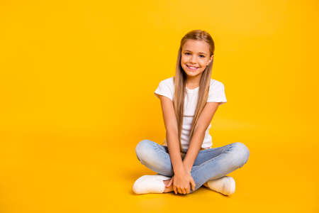 Portrait of her she nice cute sweet attractive cheerful straight-haired pre-teen girl sitting in lotus pose isolated over bright vivid shine yellow background