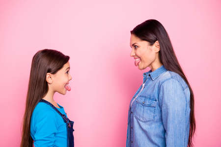 Profile side view portrait of two nice cute adorable pretty lovely attractive charming cheerful cheery positive straight-haired girls showing tongue out isolated over pink pastel background