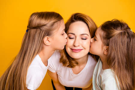 Close-up portrait of three nice cute winsome lovely sweet tender gentle attractive cheerful people kissing mum mommy having fun isolated over bright vivid shine yellow background