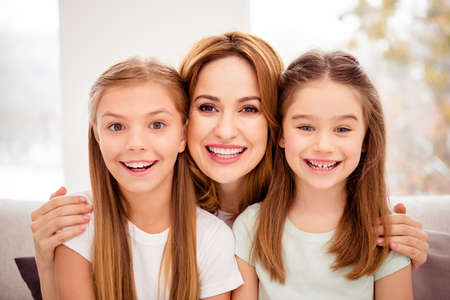 Close-up portrait of nice-looking adorable cute lovable lovely winsome attractive charming cheerful cheery people mum hugging bonding pre-teen girls in house indoors Banco de Imagens