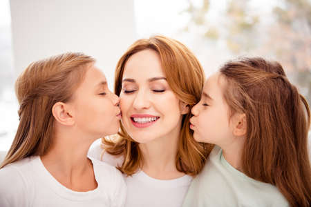 Close-up portrait of nice cute lovely adorable winsome sweet gentle tender attractive charming cheerful cheery positive redhair people mom kissing pre-teen girls in house indoors