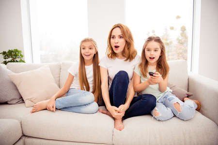 Portrait of nice cute amazed stunned lovely attractive charming cheerful cheery positive ginger hair people mom mommy mum pre-teen girls sitting on divan watching cartoon in house indoors