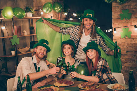 Close up photo celebrating company together st paddy day mood green leprechaun hats balloons flag table full of food eat tell speak talk toasts meet new guests decorated flat apartments Banco de Imagens