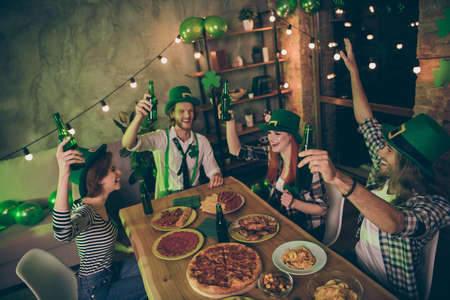 Close up photo event gathered big company friends clinking drinks green bottles hats leaf eat food pizza sausage chips ireland style party leprechaun costumes rest relax together laugh laughter