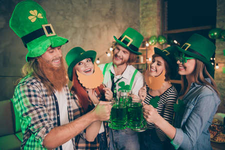 Close up photo group buddies company lucky hands arms raise alcohol wear specs national culture tradition hats checkered plaid jeans shirts false beard mustache laugh laughter festive toasting glad