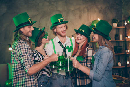 Group company cheerful five members green tradition culture national drink carefree lucky leaf style specs hats listening to toast decorated room place flat house casual shirt jeans clothes Stock Photo