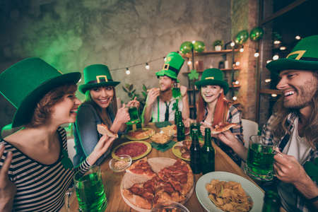 Profile side view of her she his he nice stylish cool attractive cheerful cheery positive group of people guys chatting tasting festive event amusement having fun in pub indoors Stock Photo