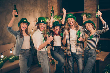Irish national celebrating leprechaun hats traditional beer brew brewery yelling company gathering festive great day off jeans outfit lucky green clover leaf on shirts yeah yes facial expressions
