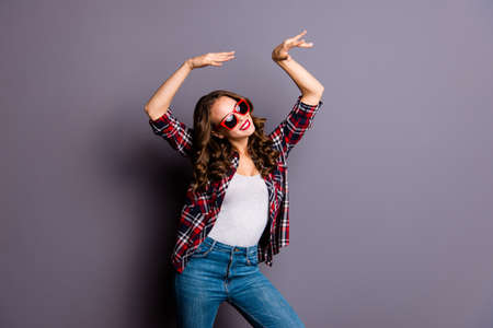 Close up portrait of an amazing  lady, hands up, on her  red dark bright summer glasses, wearing casual checkered shirt isolated on grey background