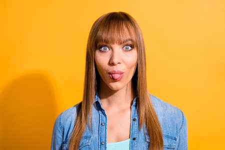attractive cheerful straight-haired lady showing tongue out isolated over bright vivid shine yellow background