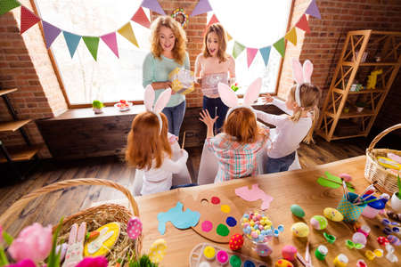 Close up back behind rear photo three small girls children day take hands arms two mom bring gift boxes glad interested curious delighted cute sweet table full craft sit big wooden table floor