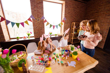 Close up photo three small girls children day wondered taste choco eggs two mommy bring gift glad presents cute table full craft sit big wooden table floor