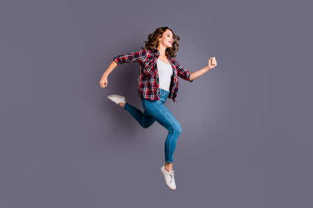 Full length size body photo of fly high attractive beautiful she her girl want to be in time for black friday sale discount wearing casual checkered plaid shirt jeans denim isolated grey background Stock Photo