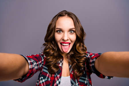 Close up portrait of amazing beautiful she her lady tongue out of mouth make funny faces take selfies do not care rules wearing specs checkered plaid shirt clothes isolated grey background Фото со стока