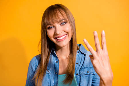 Close-up portret jej ładnej słodkiej uroczej uroczej fascynującej atrakcyjnej wesołej pani o prostych włosach pokazującej 3 środkowe palce odizolowane na jasnym, żywym połysku żółtym tle Zdjęcie Seryjne