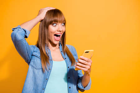 Portrait of her she nice pretty lovely attractive cheerful cheery straight-haired lady reading notification device gadget great news isolated over bright vivid shine yellow background