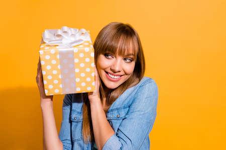 Nahaufnahme Porträt einer attraktiven Schönheit, die ihre Dame mit einer großen Geschenkbox in den Händen hält, die froh ist, sie in lässiger Jeans-Denim-Shirt-Kleidung einzeln auf gelbem Hintergrund auszupacken Standard-Bild