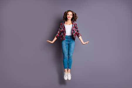 Full length size body view photo jumping high amazing attractive beautiful she her lady flight up in air pretty cute wearing casual jeans denim checkered plaid shirt grey background