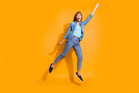 Full length body size photo yelling  in flight jumping high beautiful she lady not believe umbrella take her in sky wearing casual jeans denim shirt clothes isolated on yellow background 写真素材