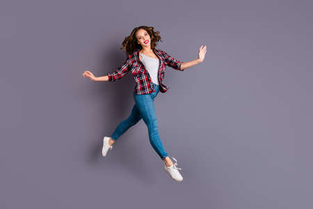 Full length size body view photo jumping high amazing attractive beautiful she her lady flight up in air not rushing pretty cute wearing casual jeans denim checkered plaid shirt grey background Banque d'images - 117001413