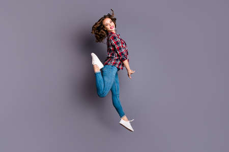 Full length size body view photo jumping high amazing attractive she her lady flight in air coquettish behaviour wearing casual jeans denim checkered plaid shirt grey background Reklamní fotografie