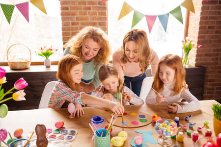 Portrait of nice cute attractive lovely sweet winsome cheerful girls making decor cool stylish things on table for event gift present in house brick loft industrial interior room
