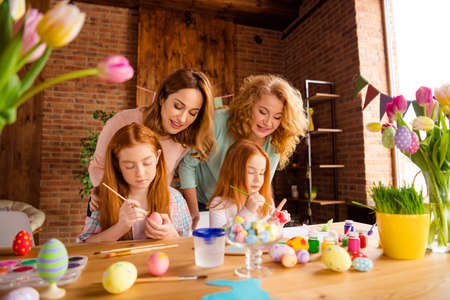 Portrait of two nice attractive cheerful ladies helping assisting two girls doing decorative things dying eggs in house brick loft industrial interior room indoors Stock Photo - 116999448
