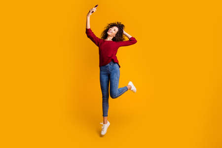 Full length body size view of her she nice cute lovely attractive cheerful slim thin fit wavy-haired lady taking making selfie having fun isolated bright vivid shine orange background.