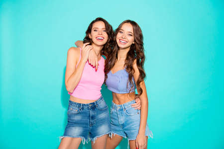 Close up portrait two stunning beautiful friendly she her lady chic hugging revealing white teeth toothy wearing pink jeans denim shorts tank tops isolated blue teal bright vivid background Stock Photo