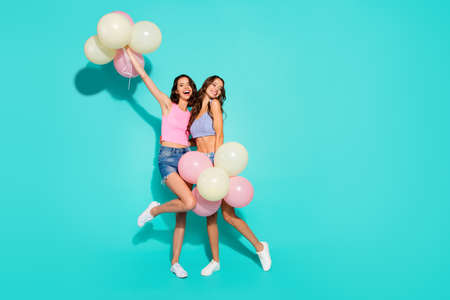 Full length body size photo funny beautiful amazing two she her ladies colored balloons hands arms raised skinny legs wearing shiny jeans denim shorts tank tops isolated teal bright vivid background Stockfoto - 117001081