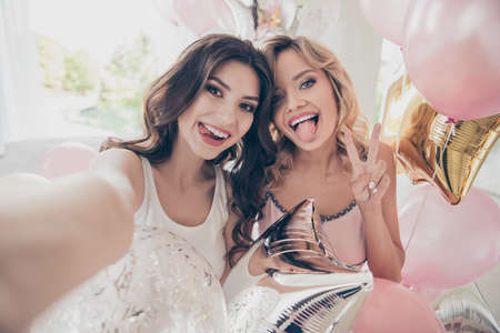 Close up portrait amazing beautiful she her ladies sitting bed pink linen sheets make take selfies show v-sign tongue out mouth flirty sleep costumes friends girls day night holiday before marriage