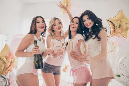 Close up photo four beautiful she her fancy ladies bed white linen sheets room hold beverage cheers dance pretty cute little drunk balloons shiny glitter sleep costumes girls day night holiday indoors