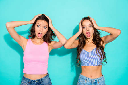 Close up portrait two amazing beautiful yelling she her lady unexpected news open mouth oh no expression arms on head wearing colored shiny shorts tank tops isolated teal bright vivid background