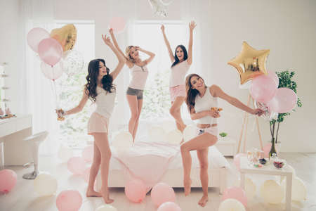 Close up photo beautiful she her fancy pretty cute classy ladies white bed linen sheets bright room balloons festive dancing queens sleep costumes girls day night holiday gathering theme party indoors 免版税图像