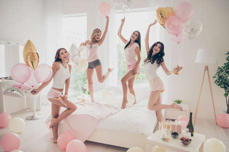 Close up photo beautiful she her fancy chic pretty cute classy ladies white bed linen sheets bright decorated room balloons dancing queens sleep costumes girls day night holiday gathering indoors