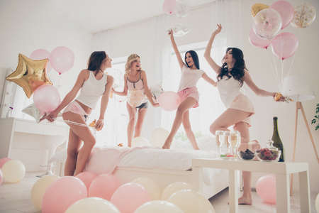 Close up low angle view photo beautiful she her fancy pretty cute classy ladies white bed dancing linen sheets bright decorated room balloons sleep costumes girls day night holiday gathering indoors