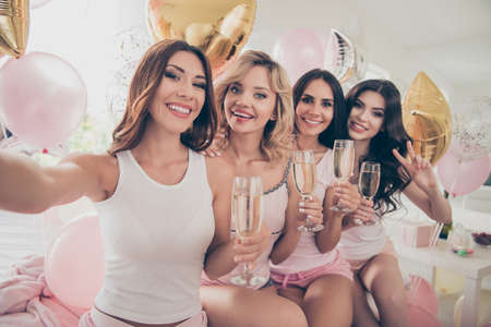 Close up photo amazing beautiful she her ladies white pink bright decorated room sit on bed chill having fun make take selfies hold gold beverage sleeping costumes girls day night holiday theme party Banco de Imagens