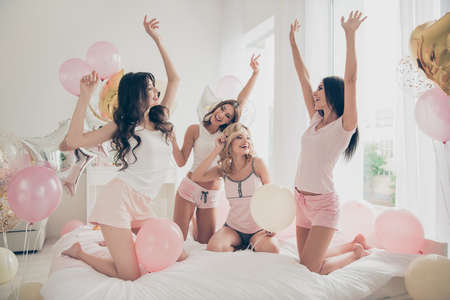 Close up photo beautiful she her fancy cute chic ladies white bed linen sheets bright decorated room yell scream shout loudly sing songs karaoke sleep costumes girls day night theme party indoors