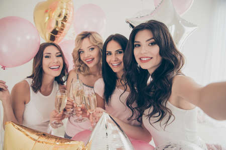 Close up photo four chill beautiful she her fancy ladies people white bright room hold golden beverage balloons festive make take selfies sleep costumes girls day night holiday meeting gathering