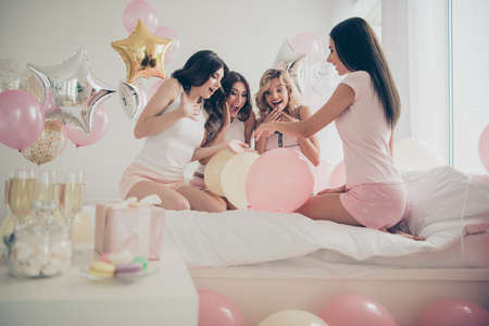 New bride with nice-looking attractive cheerful cheery ecstatic girlfriends sitting on bed looking at expensive ring in light white interior room