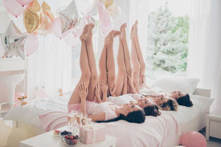 Profile side view of nice lovely attractive adorable slender fit thin slim figure girlfriends having fun lying on bed raising smooth healthy legs up in light white interior decorated house