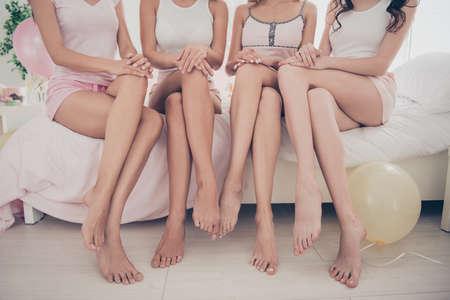 Bijgesneden weergave van mooie aantrekkelijke pasvorm dunne slanke perfecte vorm lijn goed verzorgde vriendinnen plezier zittend op bed op blote voeten in licht wit interieur ingericht huis binnenshuis