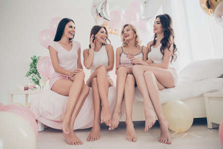 Portrait of nice attractive lovely fit thin slim well-groomed cheerful girlfriends having fun sitting on bed barefoot vacation in light white interior decorated house indoors
