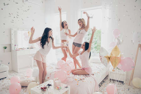 Nice-looking cool careless carefree attractive feminine charming fit thin slim graceful cheerful funny girlfriends having fun gathering meeting in light white interior decorated house