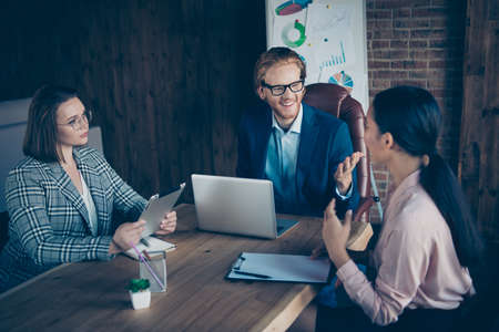 Three nice chic stylish trendy elegant cheerful business sharks discussing strategy profit growth plan economy appointment at industrial loft interior work place station Stock Photo